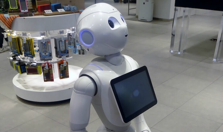 Pepper robot presenting a cell phone.