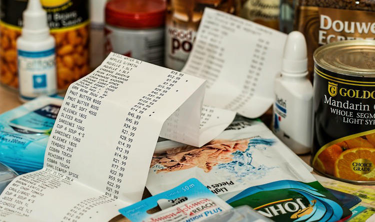 Cash register receipt surrounded by various purchased articles.